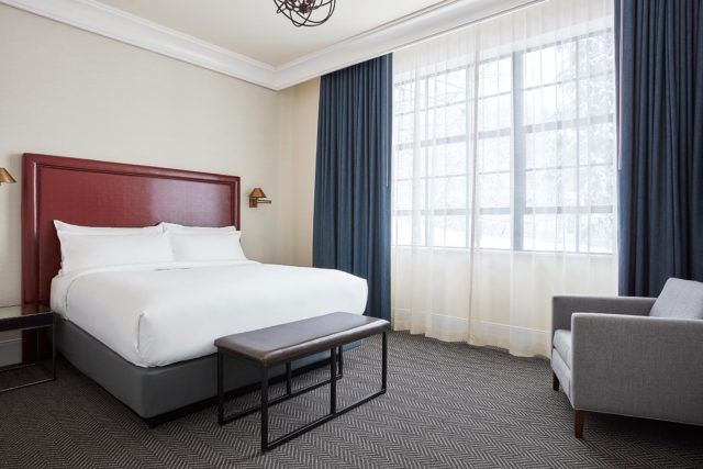 hotel room with bed featuring burgundy backboard and gray single seat chair