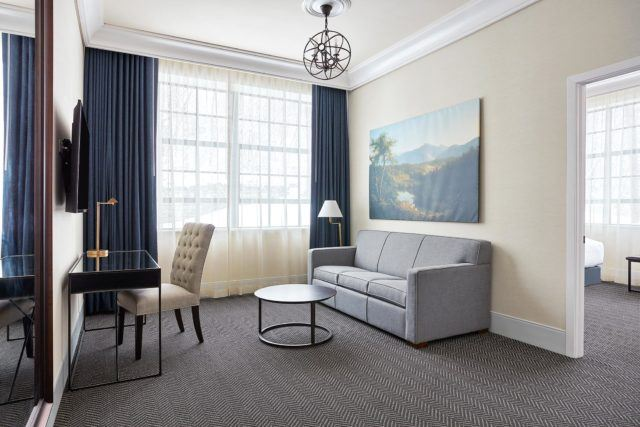 hotel room with black desk beige chair circular table and light blue couch