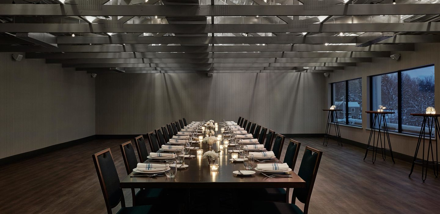 dimly lit meeting space with set long dining table