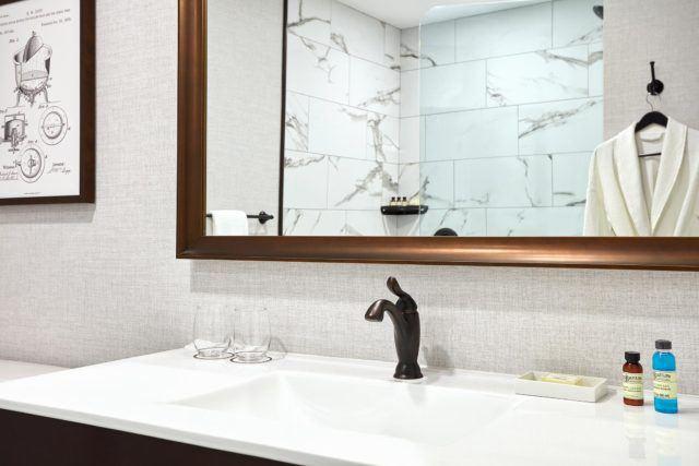 bathroom vanity with mirror featuring bronze border