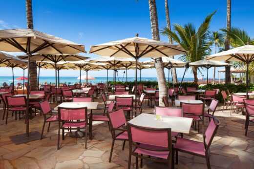 white tables and pink chairs near shoreline