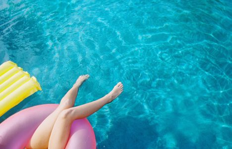 a lifestyle photo of the women in a round pink float at the pool with a yellow float aside