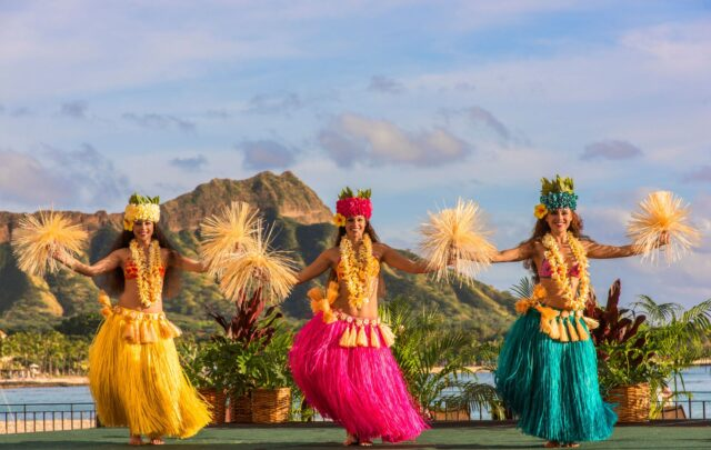 Polynesian dancers in traditional costumes performing on outdoor stage