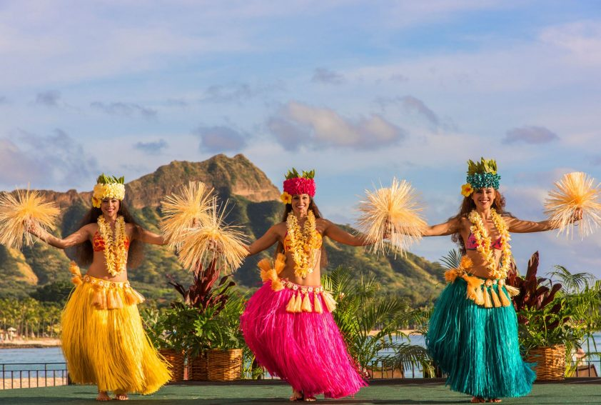 beautiful Polynesian dancers in bright colour traditional costumes performing outdoor stage with a view of diamond head