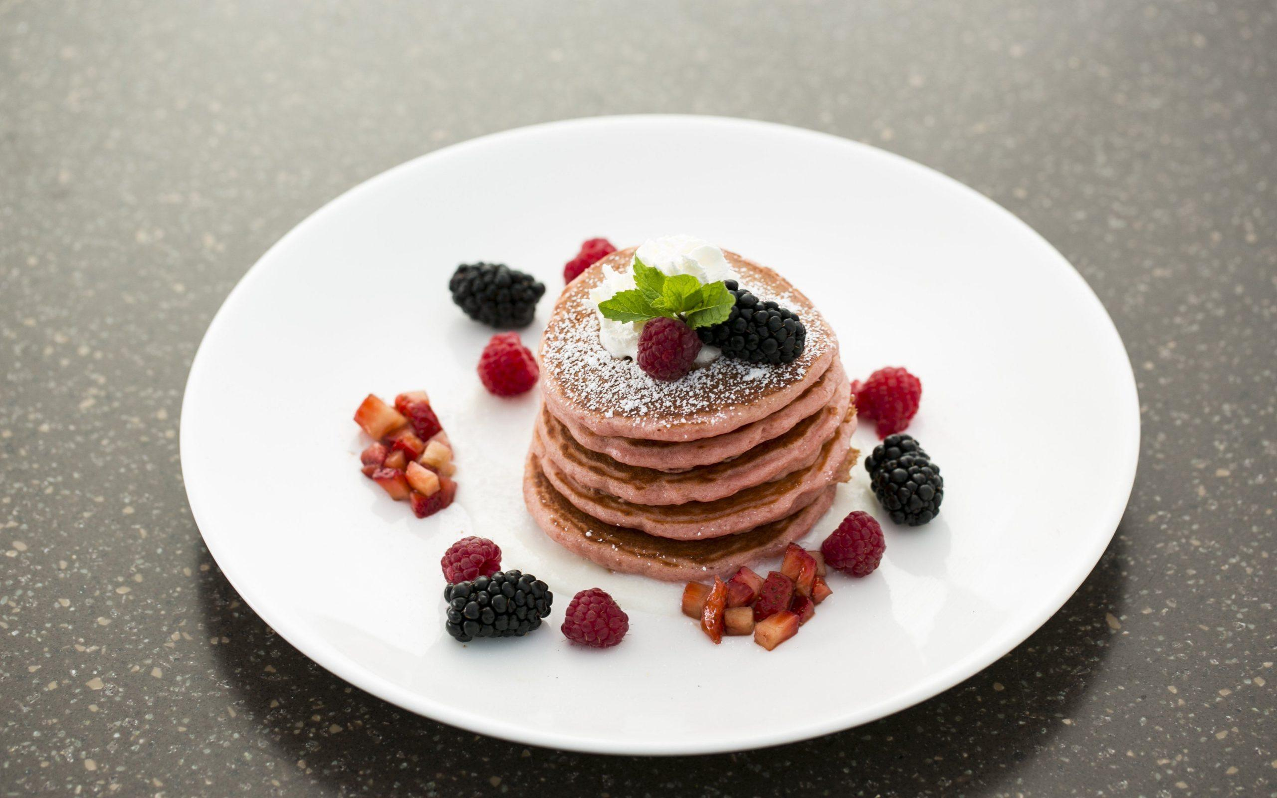 pink pancakes and berries on a plate