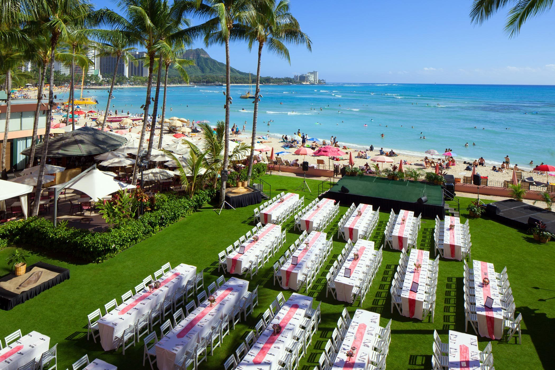 rows of tables and chairs at the resort by the beach