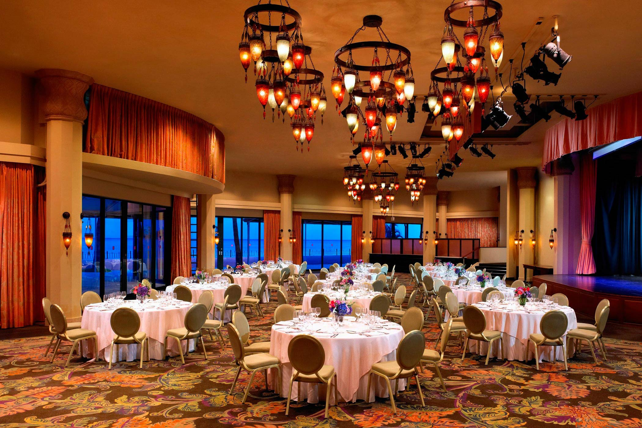 chairs and tables set up inside building with lighted chandeliers