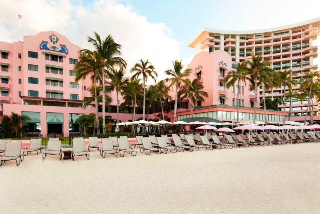 Lounge chairs setup on beach in front of hotel