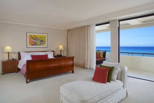 hotel suite with king bed, white day bed, and ocean view balcony