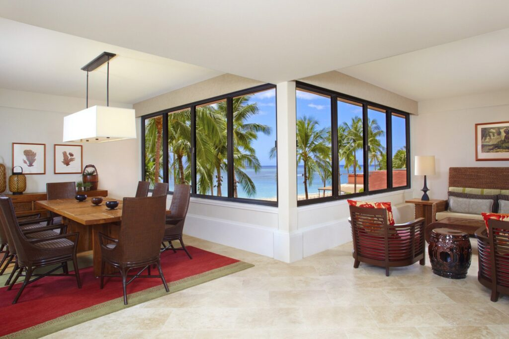 luxury hotel suite dining room with table and chairs, and large windows looking out on the ocean and palm trees