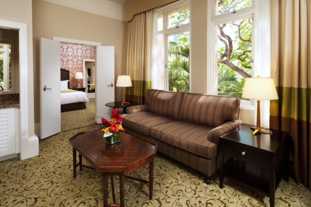 hotel suite sitting room with couch, table and garden view window