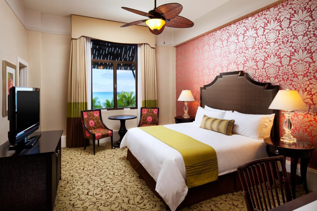 modern luxury hotel room with king bed, pink and white flowered wallpaper, and ocean view window
