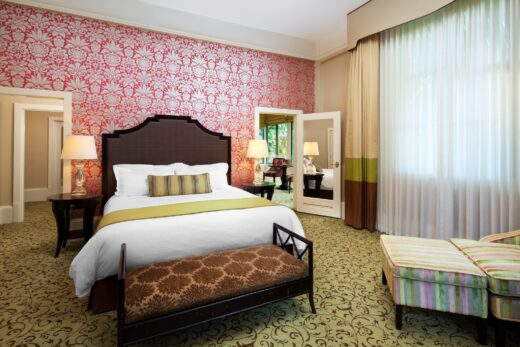 hotel room with king bed, and pink and white flowered wallpaper