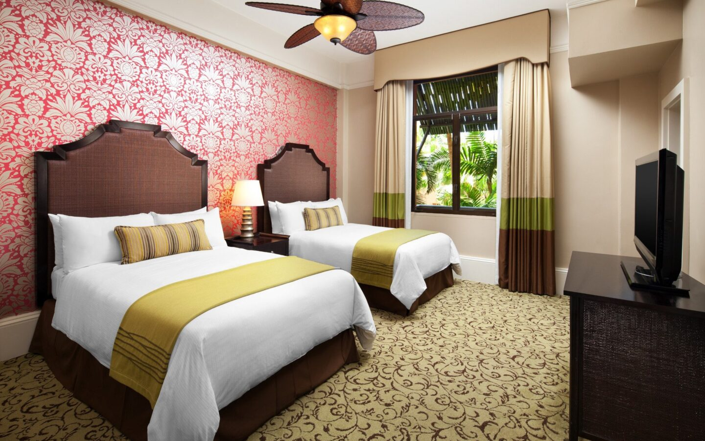 hotel room with 2 queen beds, pink and white flowered wallpaper, and garden view window