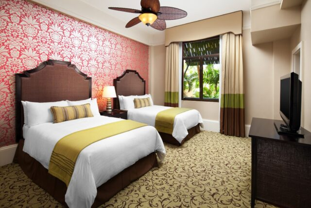 large modern luxury hotel room with 2 queen beds, pink and white flowered wallpaper, and garden view window