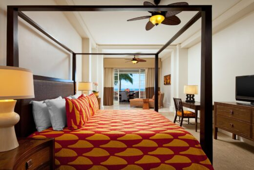 hotel suite with king size bed and an ocean view terrace with table and chairs