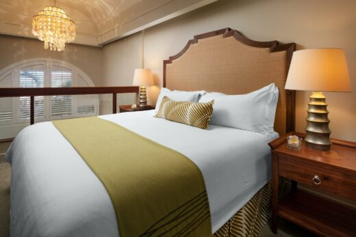 hotel room with king bed in a loft with high ceiling and chandelier