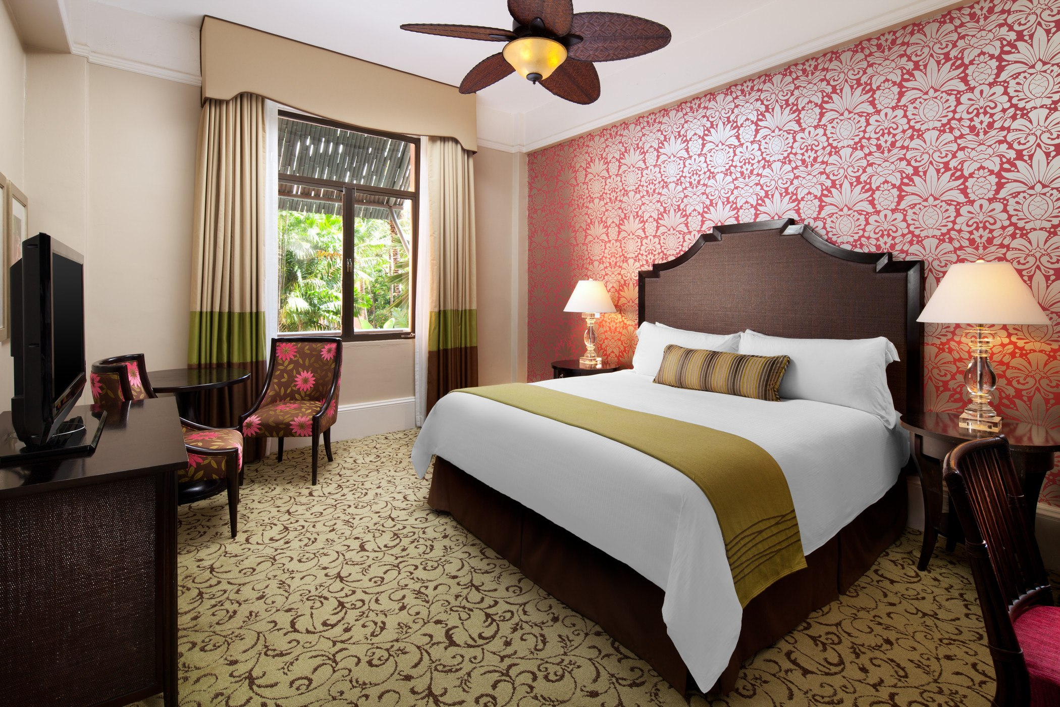 hotel room with king bed, red and white flowered wallpaper and garden view window