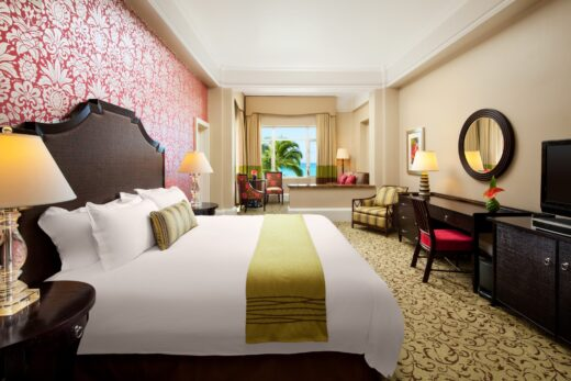 hotel room with king bed, pink and white flowered wallpaper, and ocean view window