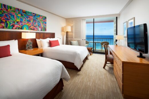 hotel room with two queen beds and an ocean view balcony