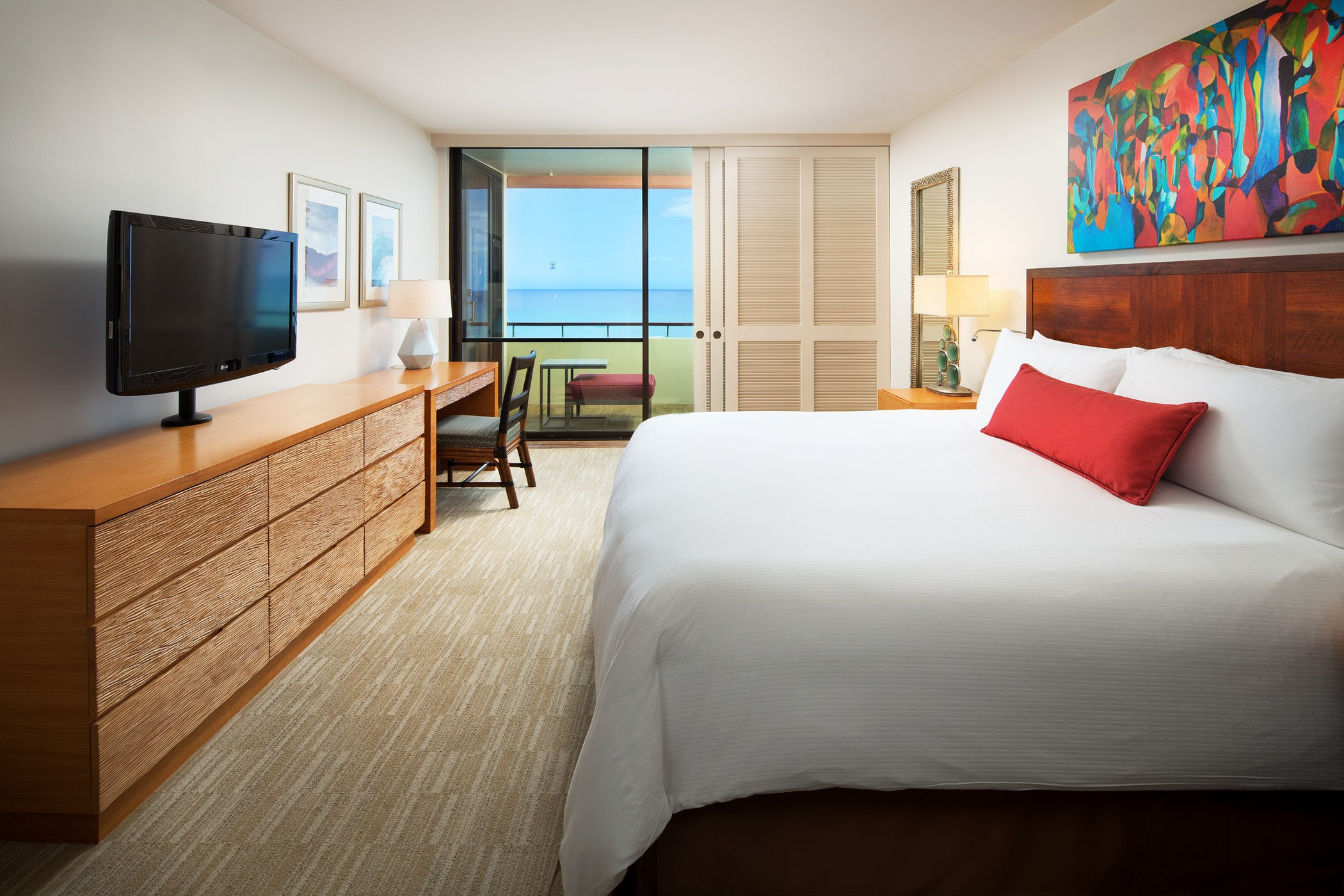 hotel suite with king bed and an ocean view balcony