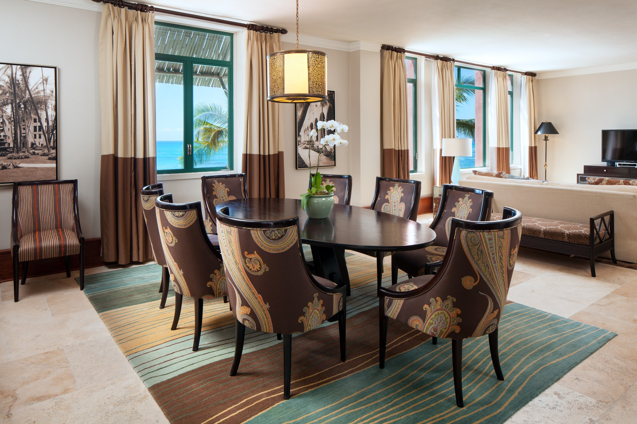 large modern luxury hotel suite dining room with table and 8 chairs, sitting area, and ocean view windows