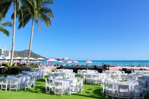 white table and chairs with stage and ocean in the background