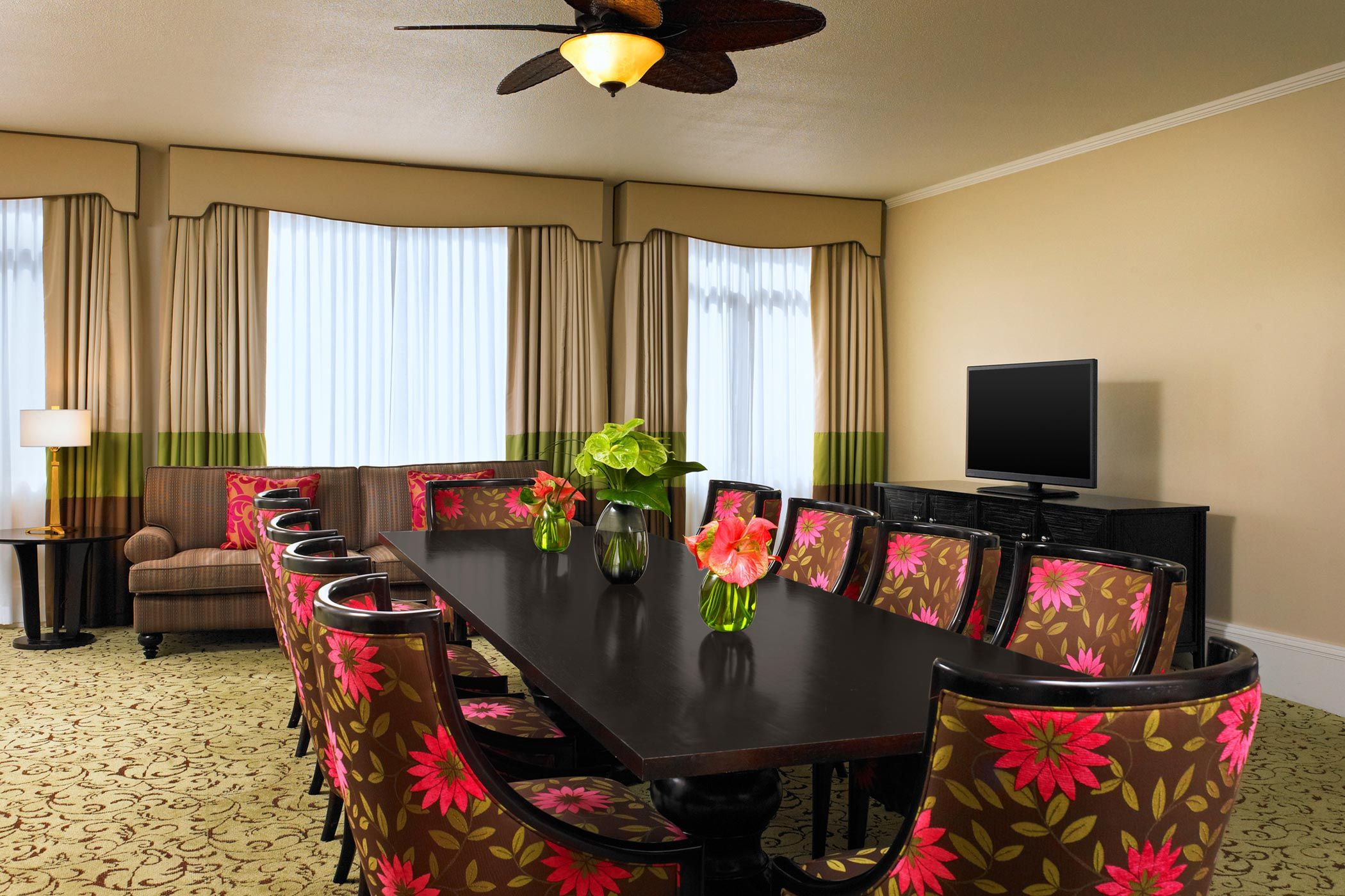 brown-and-pink floral padded chairs around long table