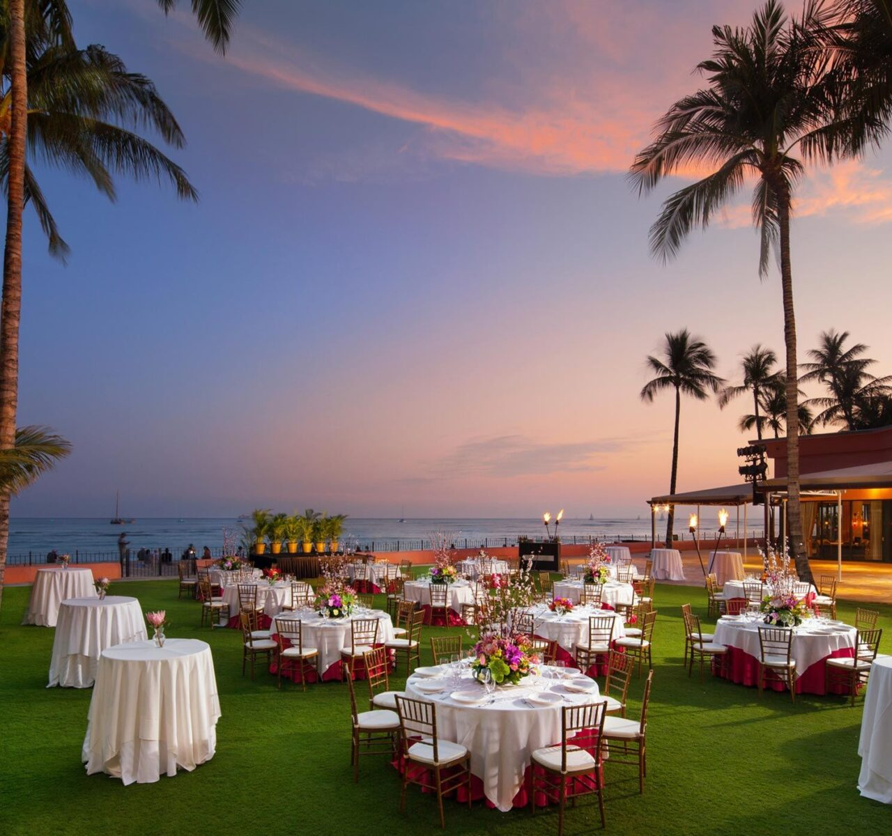 white tables setup on grass on ocean front at dusk