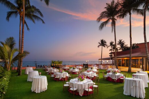 white tables setup on grass on ocean front at dusk