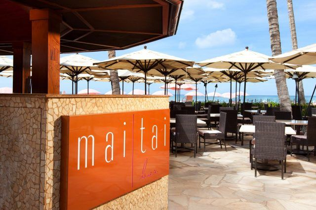 an overview of the mai tai bar in a orange signage on the left along with dining tables and white beach umbrellas