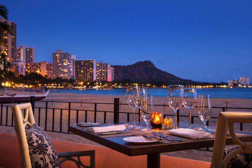 unobstructed view from the luxury dining table with wine glasses located next to the beach at night