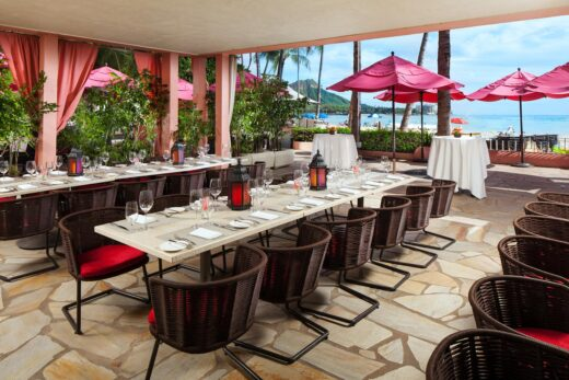 long rectangular outdoor dining table set with chairs next to a beach