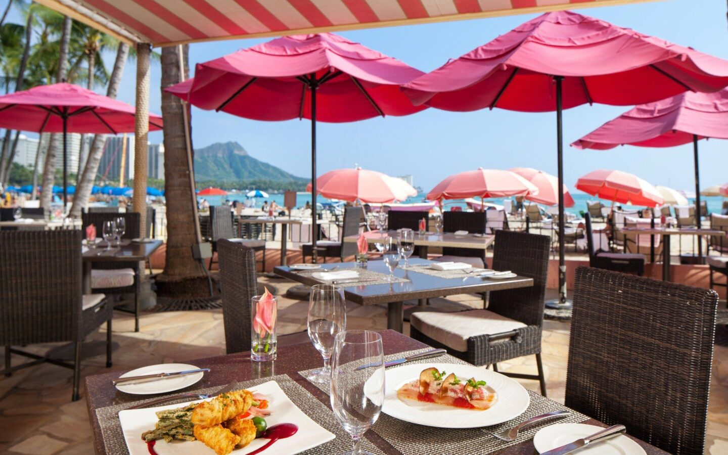 restaurant dining tables located next to the beach with big pink umbrellas