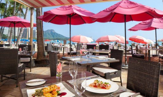 a shot at the restaurant dining table where located next to the beach with big pink parasols sparsely