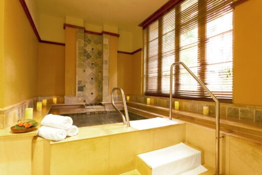 three rolled white towels beside indoor jacuzzi