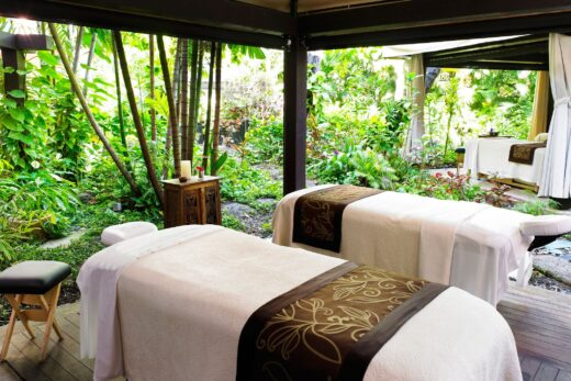 white and beige massage tables surrounded by plants