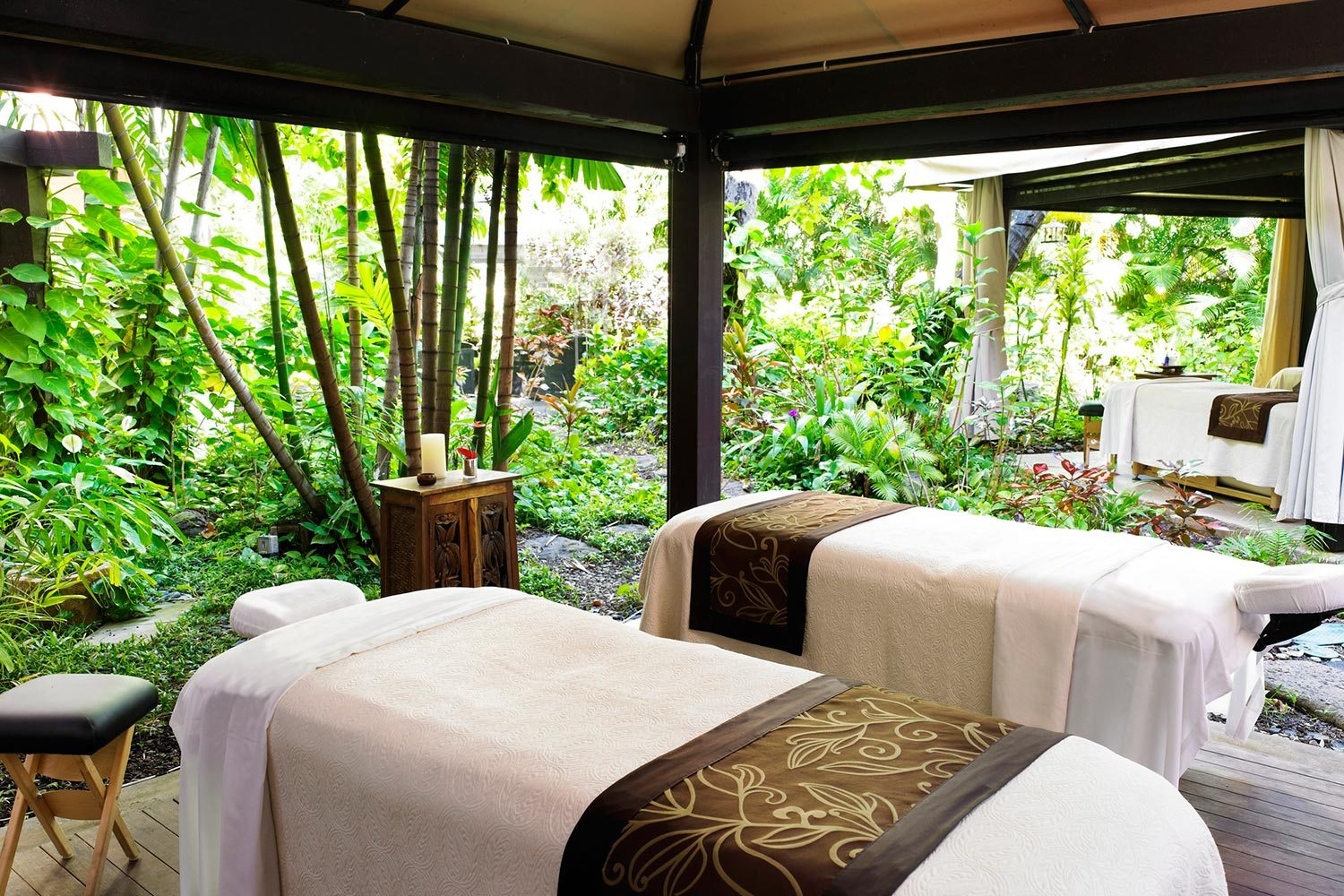 two beige massage tables in hut surrounded by plants