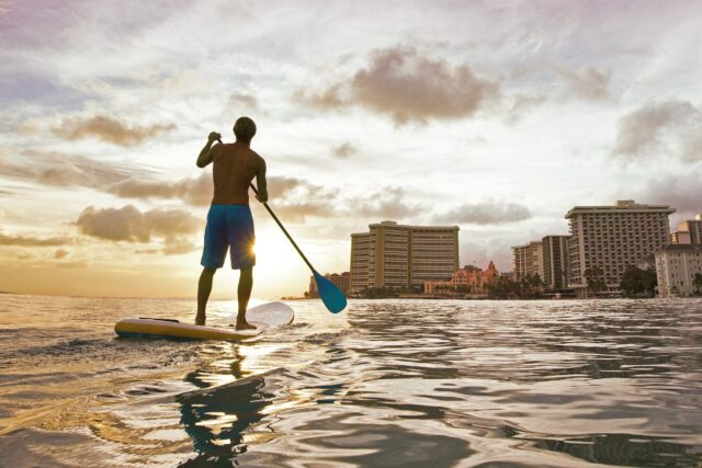 man standing on paddle board during golden hour