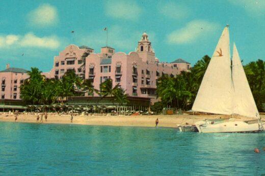 sailboat on shore in front of The Royal Hawaiian