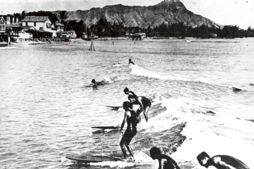 women surfing on body of water grayscale photo