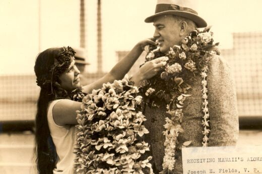 woman putting leis on man grayscale photo