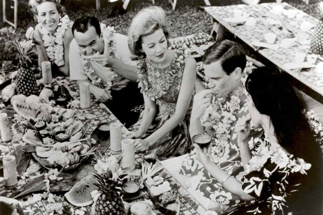 grayscale photo of five people eating