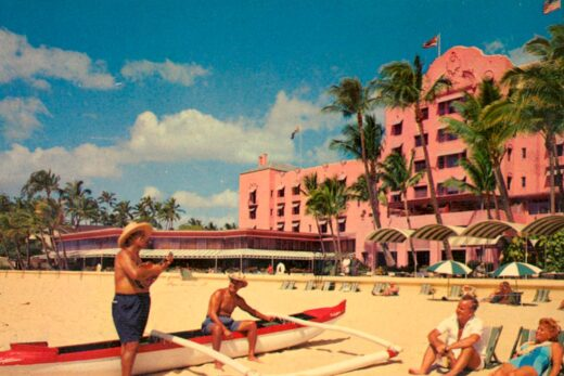 historic photo of royal hawaiian exterior with people on the beach