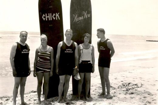 five person standing near two surfing board close-up photography