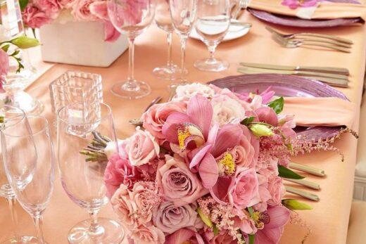 pink and white petaled flowers on wedding dining table setup