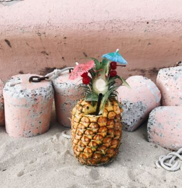 pineapple with red and blue umbrellas