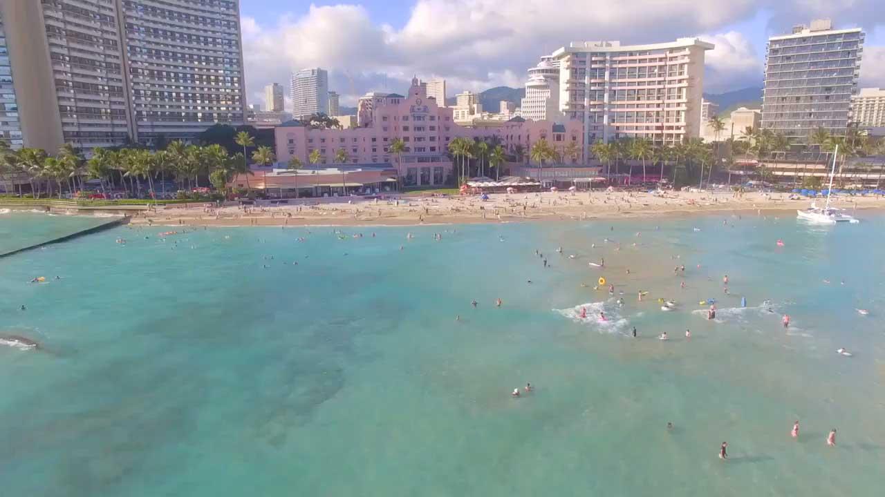 luxury resorts lining waikiki beach on a sunny day
