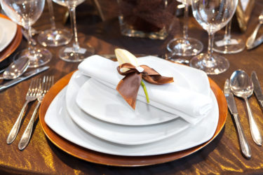 four white and brown ceramic plates beside fork, spoons, and glasses on table