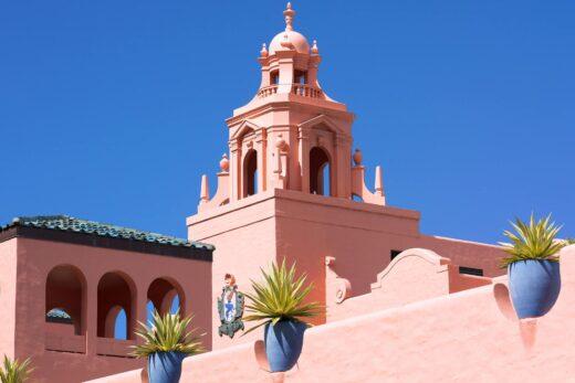 a pink palace-like resort building against a blue Hawaii sky
